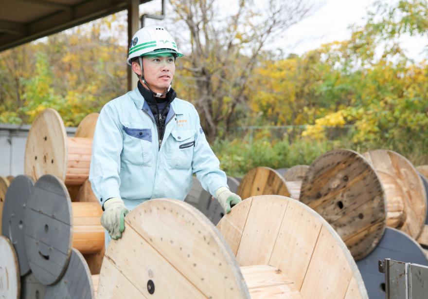 木製ドラムを運ぶ従業員