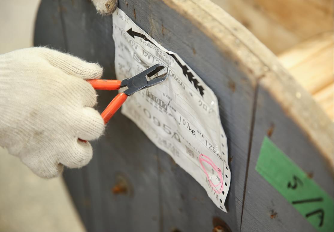 木製ドラムの荷札とと止め針を除去する様子
